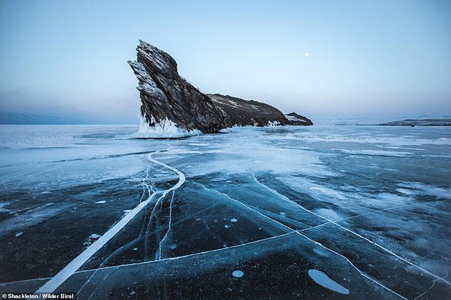 """14. Hơn 3.000 người đã bình chọn bức ảnh về hồ Baikal ở Nga của Wilder Biral trong hạng mục phong cảnh đẹp nhất. Nhiếp ảnh gia cho biết về địa điểm này: """"Đó là một địa điểm rất nổi tiếng, vì hòn đảo nhỏ này nhô ra khỏi băng trong suốt mùa đông, tạo nên vẻ ngoài giống như một đầu của một con rồng.Vào ngày này, nhiệt độ là khoảng âm 28 độ C.Tôi chuyển sang chụp tảng đá với mặt trăng phía sau. Đây là một trong những bức ảnh yêu thích của tôi sau chuyến thám hiểm""""."""