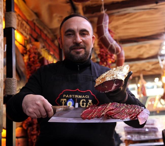 Tolga Korkutoglu, chủ cửa hàng Pastirmaci Tolga gói thịt bò đã qua chế biến được bọc trong nhiều lớp vàng lá có thể ăn được.