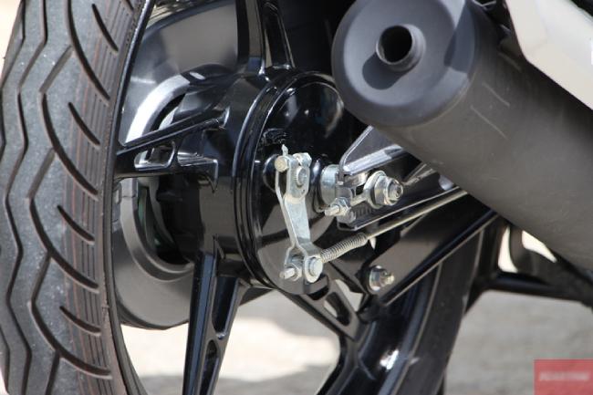 UBS hoạt động theo kiểu liên kết phanh trước và sau, giúp cân bằng lực phanh, tăng độ an toàn cho lái xe. Điều này rất cần thiết cho người mới lái xe máy, hoặc những ai ưa thích tốc độ và đi phượt. Ảnh ống xả và vành bánh sau của Yamaha FINN 115i.