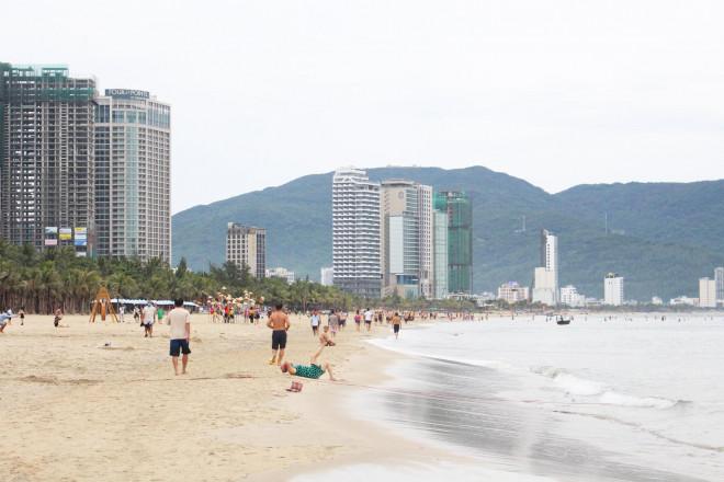 Đà Nẵng gỡ lệnh cấm, người dân bịt kín khẩu trang tắm biển từ tinh mơ - 1