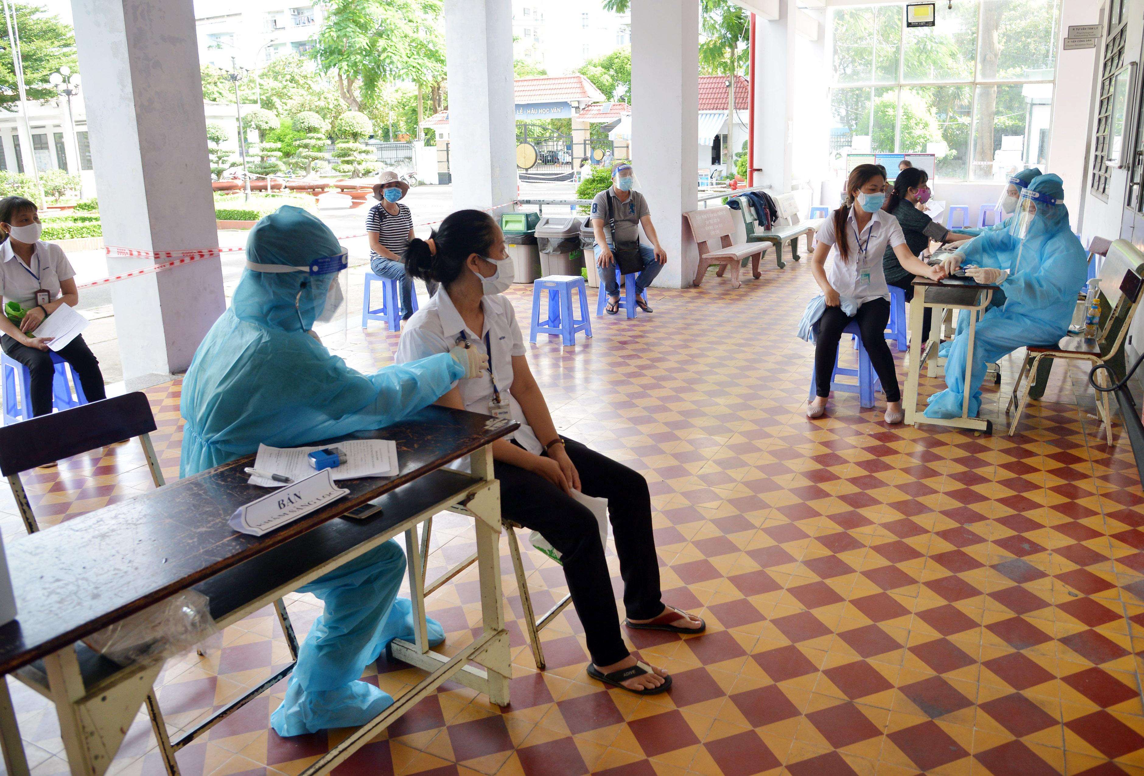 Ảnh: Người dân TP.HCM xếp hàng giãn cách tiêm vắc xin ngừa COVID-19 - 7