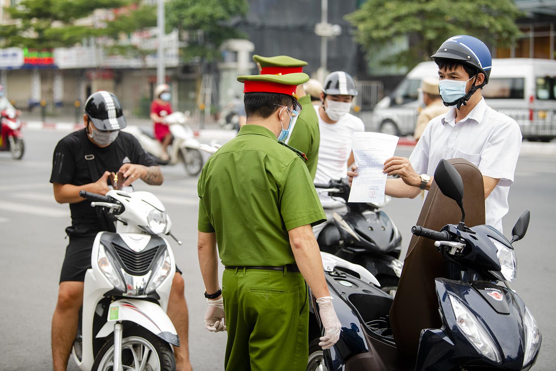 Hà Nội: Lực lượng chức năng nhắc nhở người đi đường xuất trình thêm lịch trực, lịch làm việc - 3