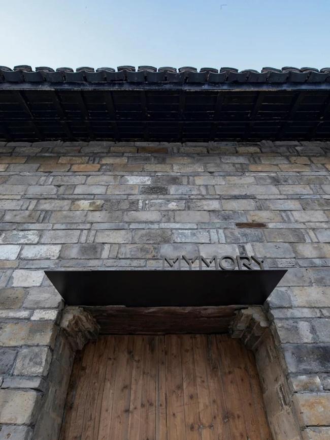 Tường bên ngoài được sửa sang lại, nhóm thiết kế đã đưa các viên gạch màu xám ốp ngoài bức tường gợi nhớ đến phong cách xưa của làng.
