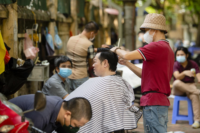 Ngày đầu nới lỏng giãn cách, thợ cắt tóc làm mỏi tay không hết việc - 2